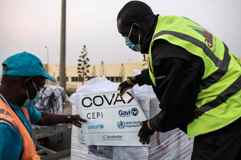 Workers start to un-wrap boxes containing Oxford/AstraZeneca vaccines donated to Senegal by the Covax global Covid-19 vaccination program are seen as they are unloaded in Dakar on March 3, 2021. - Covax is a global scheme to procure and distribute inoculations for free, as the world races to contain the pandemic. (Photo by JOHN WESSELS / AFP)