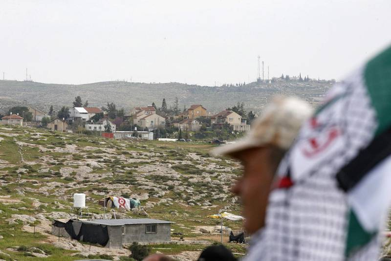 A Palestinian man takes part in a protest in the Palestinian village of Susya, south of Yatta town, in the occupied West Bank on March 14, 2021, against the visit of the Israeli Prime Minister to the Israeli settlement of Susya (background).  / AFP / HAZEM BADER