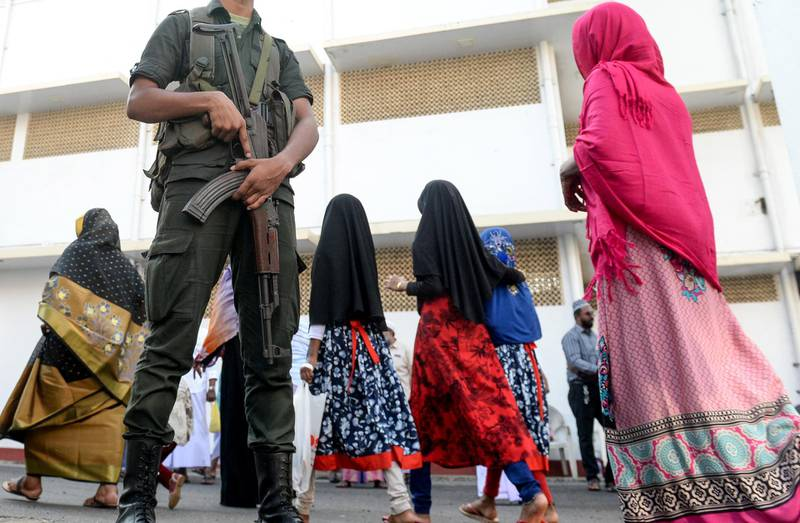 Sri Lankan Army personnel stand guard as Muslim devotees arrive to offer prayers on the first day of Eid al-Fitr at the Grand Mosque in Colombo on July 5, 2019. - Muslims around the world are celebrating the Eid al-Fitr festival, which marks the end of the fasting month of Ramadan. (Photo by LAKRUWAN WANNIARACHCHI / AFP)