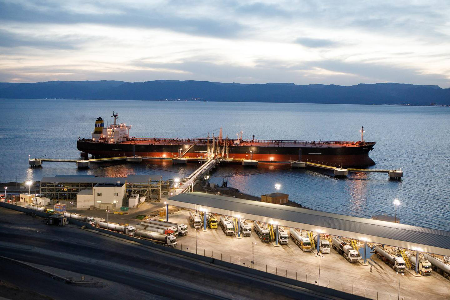 Tanker trucks fill up with crude oil for delivery to the Jordan Petroleum Refinery Co. on the quayside near a crude oil tanker, operated by Navigator Gas LLC, at Aqaba port, operated by Aqaba Development Corp., in Aqaba, Jordan, on Wednesday, April 11, 2018. Both the LNG and the liquefied petroleum gas (LPG) terminals were developed to secure the supply of gas resources after the disruption in Egyptian natural gas imports in 2010. Photographer: Annie Sakkab/Bloomberg