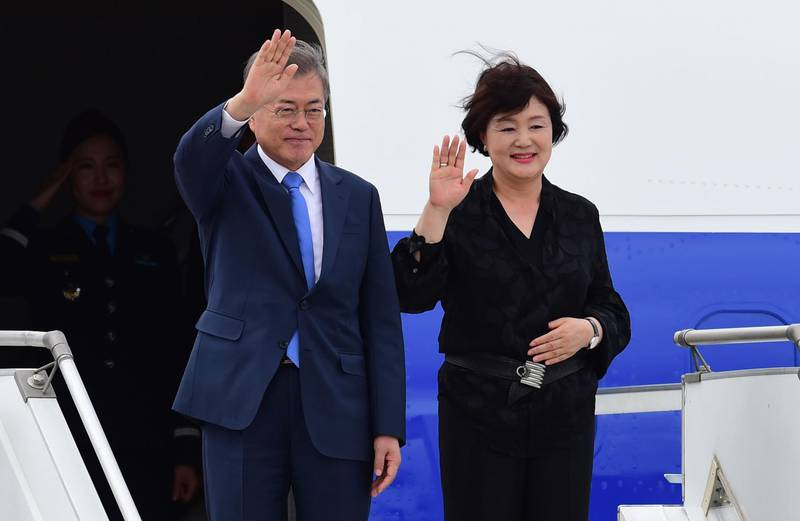 South Korea's President Moon Jae-in  (L) and his wife Kim Jung-sook, wave upon arrival at Ezeiza International airport in Buenos Aires province, on November 29, 2018. Global leaders gather in the Argentine capital for a two-day G20 summit beginning on Friday likely to be dominated by simmering international tensions over trade. / AFP / MARTIN BERNETTI