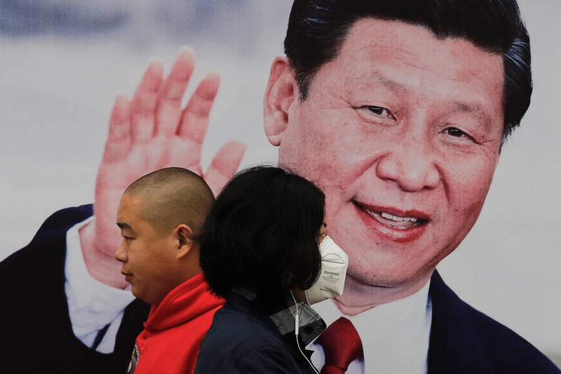 Pedestrians, one wearing a mask, walk by a poster of Chinese President Xi Jinping on a street in Beijing, Thursday, Oct. 26, 2017. China's ruling Communist Party has praised President Xi as a Marxist thinker, adding to intense propaganda promoting Xi's personal image as he begins a second five-year term as leader. (AP Photo/Andy Wong)