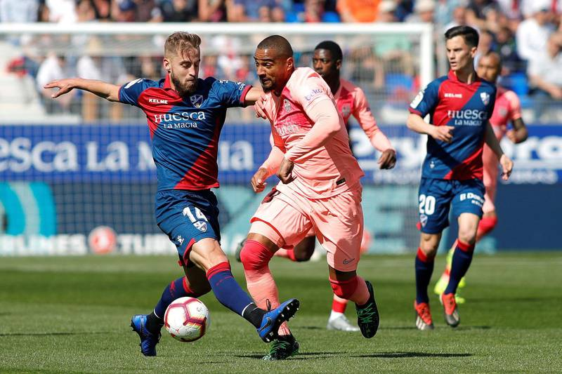 epa07503922 FC Barcelona's Kevin-Prince Boateng (R) in action against SD Huesca's Jorge Pulido (L) during the Spanish LaLiga soccer match between SD Huesca and FC Barcelona at El Alcoraz stadium in Huesca, Aragon, northern Spain, 13 April 2019.  EPA/ELENA MUNOZ