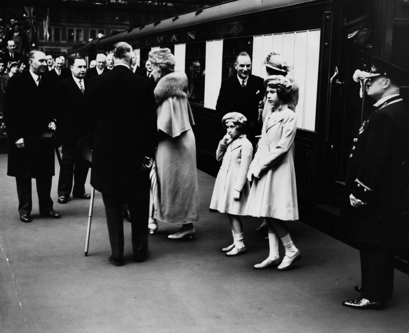 British princesses Elizabeth (right) and Margaret standing together on the train platform as they see off their parents, King George VI and Queen consort Elizabeth, at Waterloo Station, London, May 6th 1939. (Photo by Fox Photos/Hulton Archive/Getty Images)