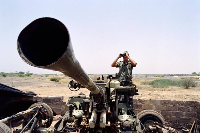 A French soldier looks through binoculars as he mans an anti-craft gun near Djibouti airport, on August 20, 1990, as French army was deployed in the Persian Gulf since Iraq's invasion of Kuwait on August 02, 1990, leading to a conflict between Iraq and Koweit and an international military intervention. (Photo by Charles CARATINI / AFP)