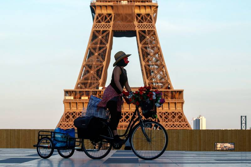 FILE PHOTO: A woman, wearing a mask, rides her bicycle near the Eiffel tower at Trocadero square in Paris during the nationwide curfew, from 7 p.m to 6 a.m, due to tighter measures against the spread of coronavirus disease (COVID-19) in France, April 26, 2021. REUTERS/Gonzalo Fuentes/File Photo