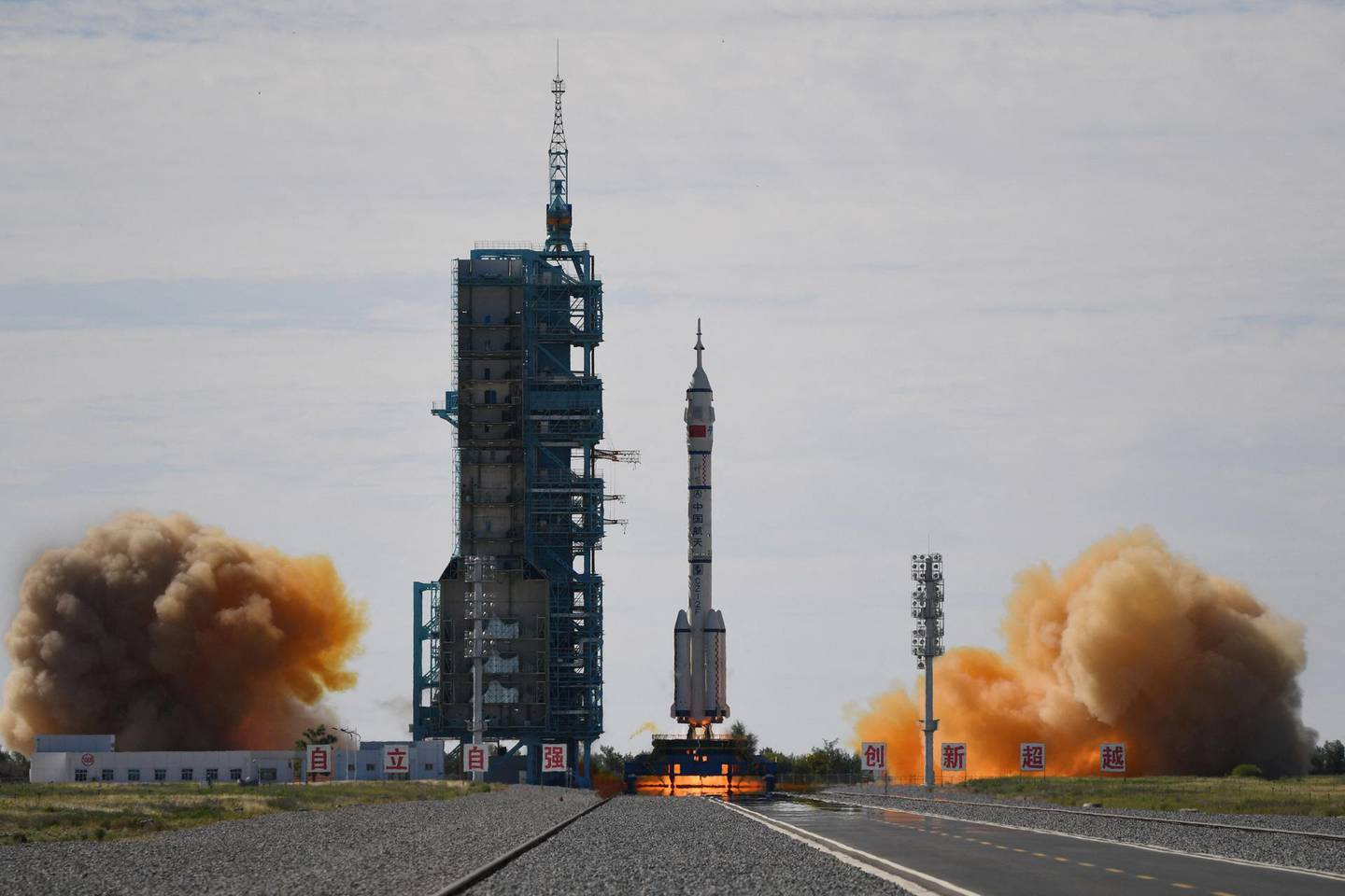 A Long March-2F carrier rocket, carrying the Shenzhou-12 spacecraft and a crew of three astronauts, lifts off from the Jiuquan Satellite Launch Centre in the Gobi desert in northwest China on June 17, 2021, the first crewed mission to China's new space station.  / AFP / GREG BAKER