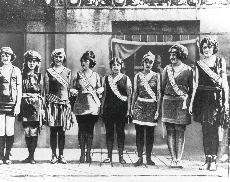 1921:  Full-length portrait of the first Miss America contestants, wearing their sashes over swimsuits, standing in a line on the boardwalk in Atlantic City, New Jersey. Margaret Gorman (second from left), Miss Washington, D.C., was the winner.  (Photo by Hulton Archive/Getty Images)