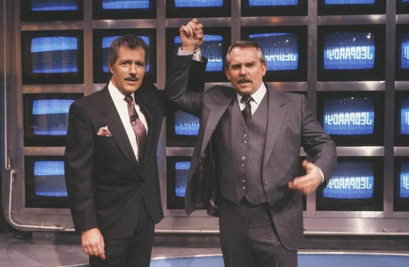 "CHEERS -- ""What is... Cliff Clavin?"" Episode 14 -- Air Date 01/18/1990 -- Pictured: (l-r) Alex Trebek as Himself, John Ratzenberger as Cliff Clavin-- Photo by: Kim Gottlieb-Walker/NBCU Photo Bank"