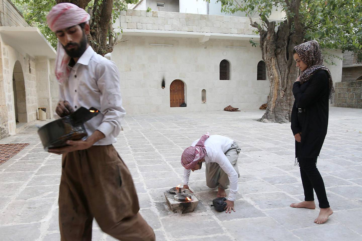 Yazidi woman Ashwaq Haji (R), allegedly used by the Islamic State group (IS) as a sex slave, visits the Lalish temple in tribute to the jihadists' victims from her village of Kocho near Sinjar, in Lalish, northern Iraq, on August 15, 2018. - A young Yazidi woman who fled to Germany but returned home to northern Iraq says she cannot escape her Islamic State group captor who held her as a sex slave for three months.  Ashwaq Haji, 19, says she ran into the man in a German supermarket in February. Traumatised by the encounter, she returned to Iraq the next month. Like many other Yazidis, she was kidnapped by IS when the jihadists seized swathes of Iraq in the summer of 2014. (Photo by - / AFP)