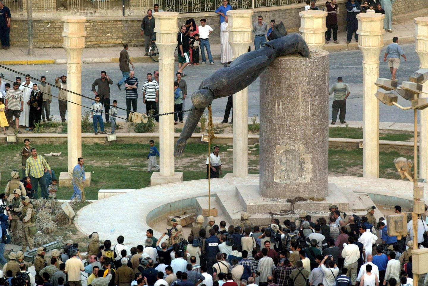 (FILES) In this file photo taken on April 9, 2003 Iraqis watch a statue of Iraqi President Saddam Hussein falling in Baghdad's al-Fardous (paradise) square. On April 9, 2003, the US-led coalition overthrew Saddam Hussein. Fifteen years after the invasion, life in Iraq has been transformed as sectarian clashes and jihadist attacks have divided families and killed tens of thousands of people, leaving behind wounds that have yet to heal and a lagging economy. / AFP PHOTO / Patrick BAZ