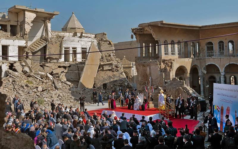 """Pope Francis speaks at a square near the ruins of the Syriac Catholic Church of the Immaculate Conception (al-Tahira-l-Kubra), in the old city of Iraq's northern Mosul on March 7, 2021.  Pope Francis, on his historic Iraq tour, visits today Christian communities that endured the brutality of the Islamic State group until the jihadists' """"caliphate"""" was defeated three years ago / AFP / Vincenzo PINTO"""