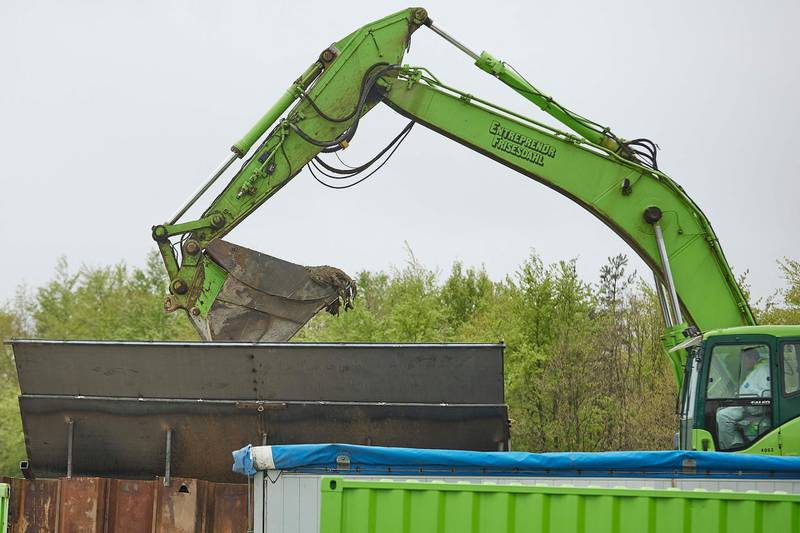 A excavator loads in a container buried mink for incineration during a trial excavation at a military area close to Norre Felding, Holstebro, in Denmark, on May 13, 2021. Denmark on Thursday kicked off the grisly task of unearthing and incinerating minks that were hastily buried after a mass culling sparked by fears of a mutated coronavirus strain, authorities said. - Denmark OUT  / AFP / Ritzau Scanpix / Mikkel Berg Pedersen
