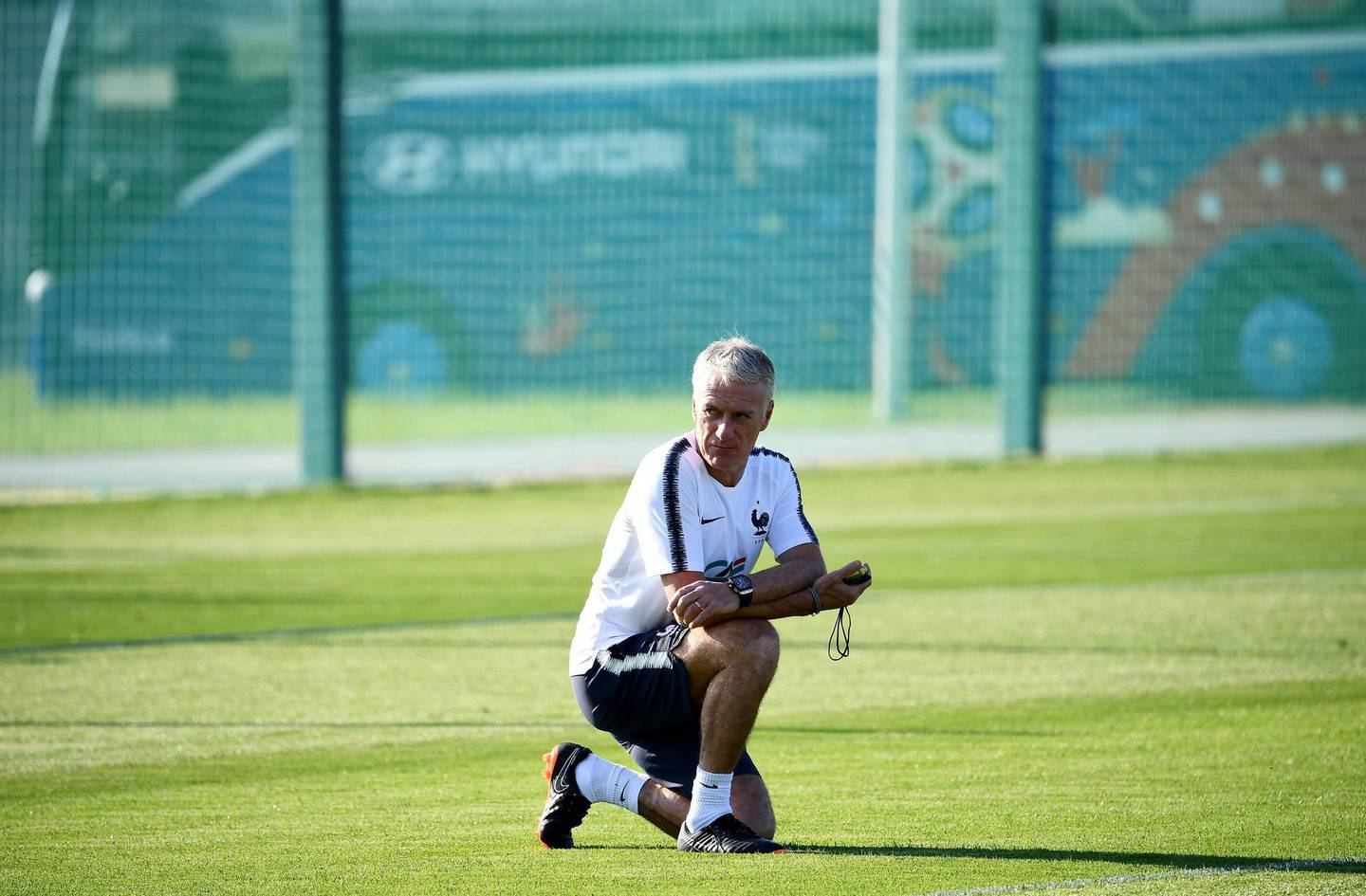 France's head coach Didier Deschamps kneels on the pitch during a training session in Istra, west of Moscow on June 27, 2018, during the Russia 2018 World Cup football tournament. / AFP / FRANCK FIFE