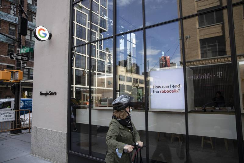 A person on a scooter passes in front of the Google Store Chelsea in New York, U.S., on Friday, May 28, 2021. The Google Store will display and sell a variety of product such as Pixel phones, Nest smart home devices, Fitbit trackers, Pixelbooks, and more. Photographer: Victor J. Blue/Bloomberg