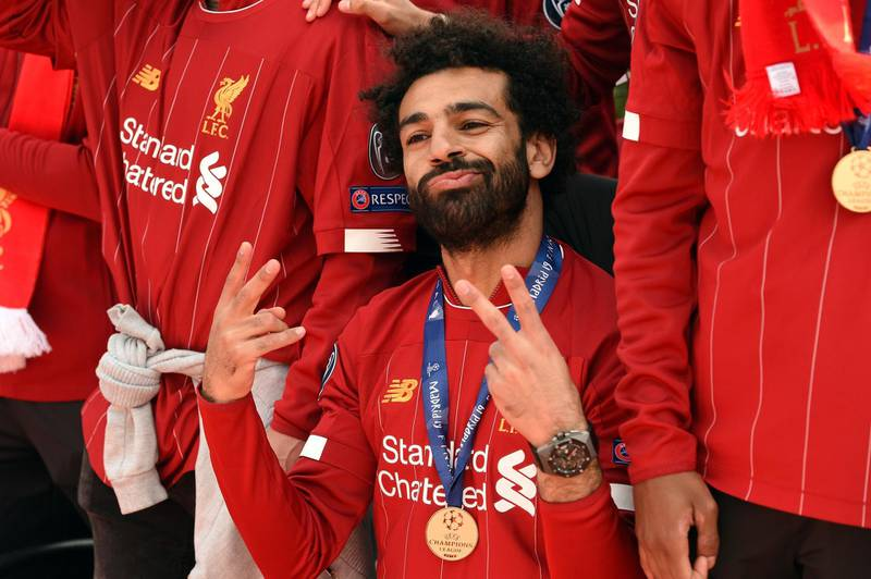 Liverpool's Egyptian midfielder Mohamed Salah gestures to the fans during an open-top bus parade around Liverpool, north-west England on June 2, 2019, after winning the UEFA Champions League final football match between Liverpool and Tottenham. Liverpool's celebrations stretched long into the night after they became six-time European champions with goals from Mohamed Salah and Divock Origi to beat Tottenham -- and the party was set to move to England on Sunday where tens of thousands of fans awaited the team's return. The 2-0 win in the sweltering Metropolitano Stadium delivered a first trophy in seven years for Liverpool, and -- finally -- a first win in seven finals for coach Jurgen Klopp. / AFP / Oli SCARFF
