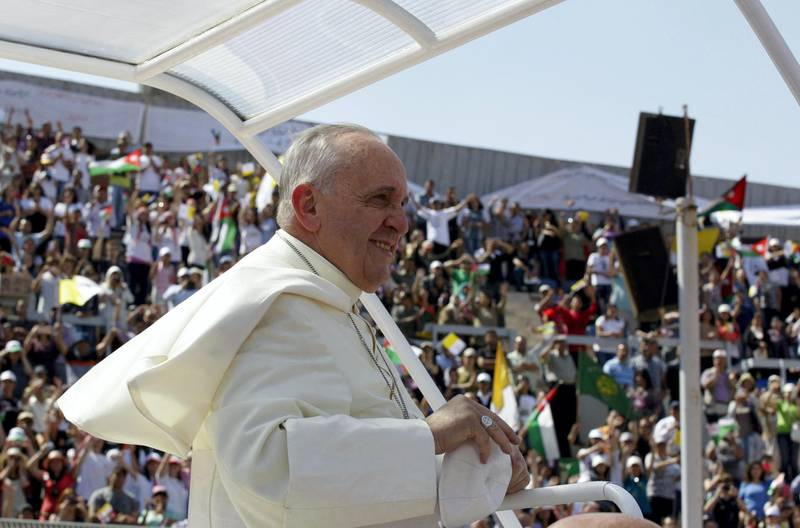 Pope Francis greets the crowd before celebrating a mass at the Amman stadium in the Jordanian capital on May 24, 2014. Pope Francis made an urgent plea today for peace in war-torn Syria as he kicked off a three-day pilgrimage to the Middle East. AFP PHOTO / KHALIL MAZRAAWI (Photo by KHALIL MAZRAAWI / AFP)