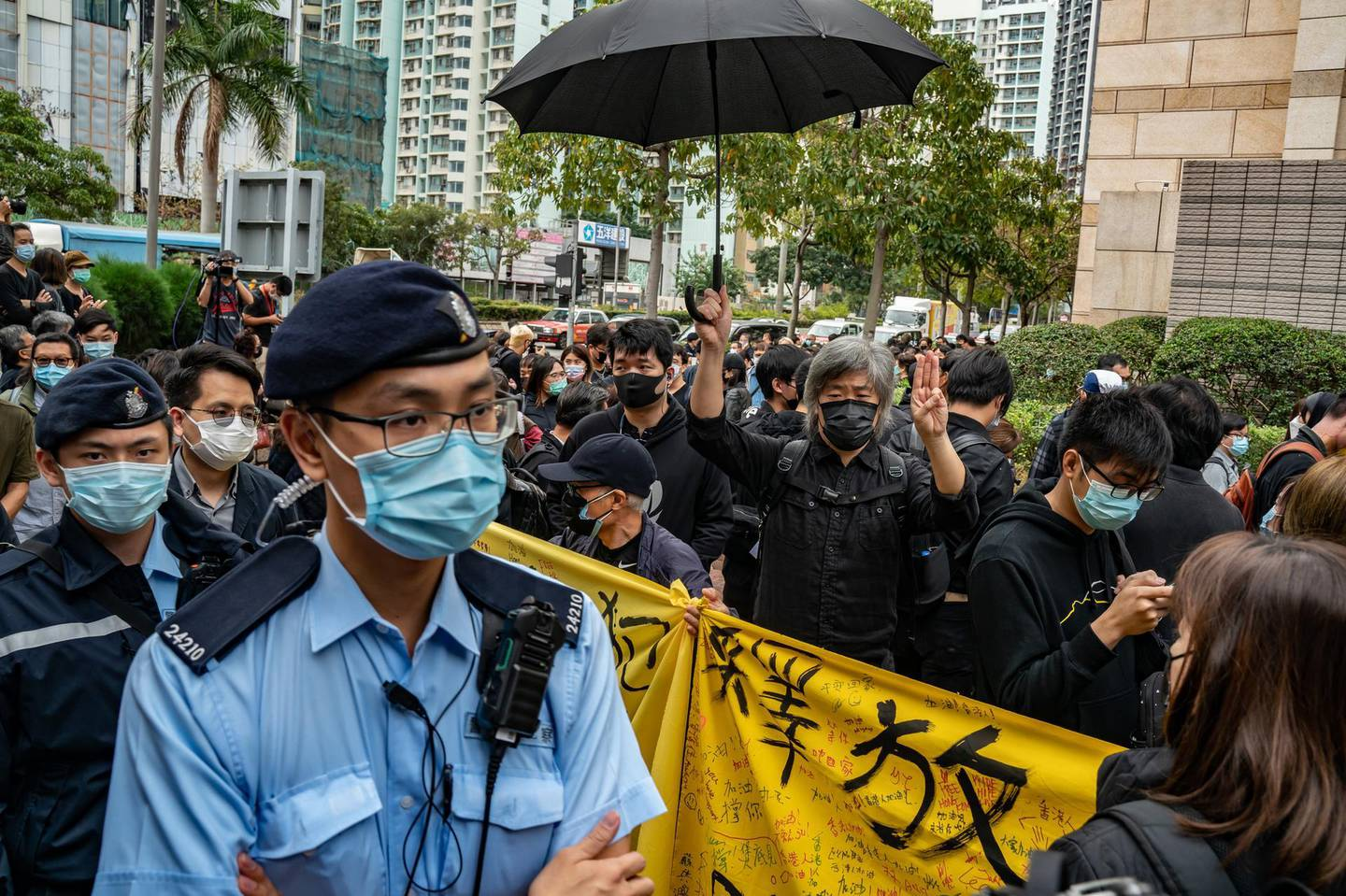 HONG KONG, HONG KONG - MARCH 1: Pro-democracy supporters line up outside the West Kowloon court as police officers patrol on March 1, 2021 in Hong Kong. The protest took place during the court appearances by dozens of dissidents charged with subversion in the largest use of Beijing's sweeping new the national security law to date. (Photo by Anthony Kwan/Getty Images)
