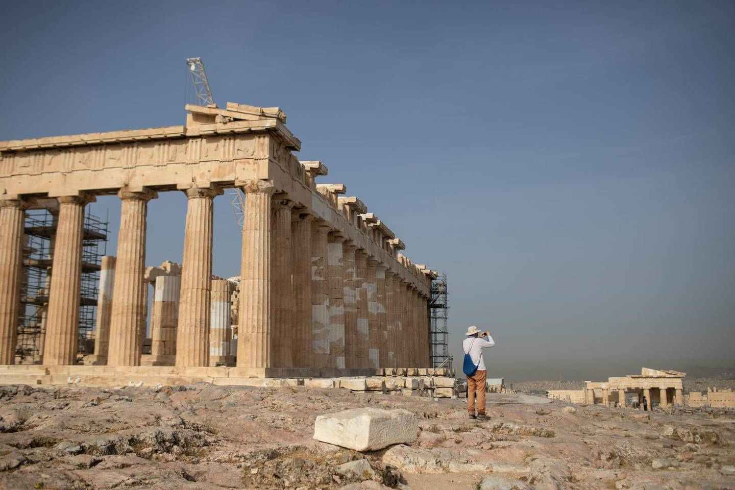 A man takes picture next the ancient Parthenon temple at the Acropolis hill of Athens, on Monday, May 18, 2020. Greece reopened the Acropolis in Athens and other ancient sites Monday, along with high schools, shopping malls, and mainland travel in the latest round of easing pandemic restrictions imposed in late March. (AP Photo/Petros Giannakouris)