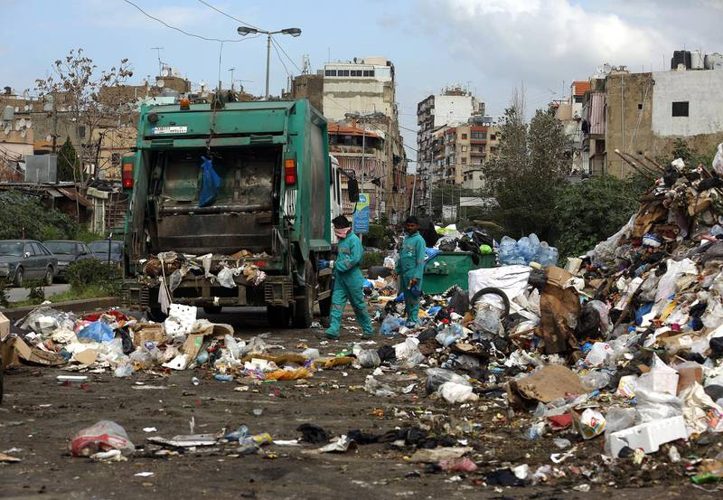 Asian employees from Sukleen, a local trash management company, collect garbage from a temporary garbage dump in an eastern suburb of the Lebanese capital, Beirut, on March 4, 2016. (Photo by PATRICK BAZ / AFP)