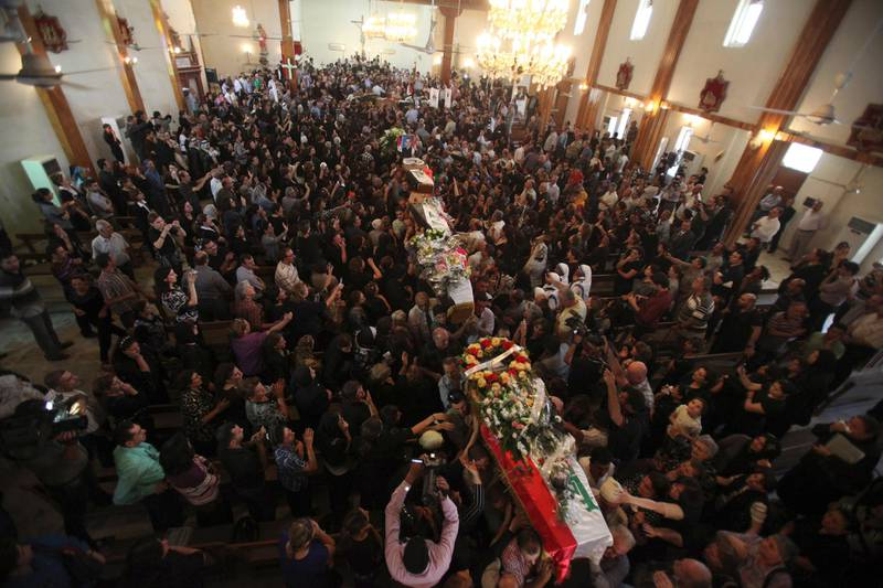 Residents carry coffins of victims killed in an attack on the Our Lady of Salvation Church, during a funeral at St. Joseph Chaldean Church in Baghdad November 2, 2010. Iraq launched an investigation on Tuesday into a church raid in which 52 hostages and police were killed, trying to find out how al Qaeda-linked gunmen managed to storm the building despite checkpoints, an official said.   REUTERS/Saad Shalash (IRAQ - Tags: SOCIETY CRIME LAW IMAGES OF THE DAY)