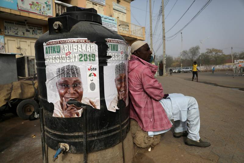 FILE PHOTO: A man sits next to a campaign poster of Atiku Abubakar, leader of the People's Democratic Party (PDP), after the postponement of the presidential election in Kano, Nigeria February 17, 2019. REUTERS/Luc Gnago/File Photo