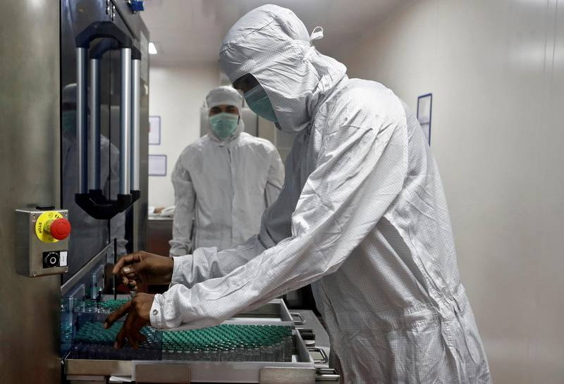 FILE PHOTO: An employee in personal protective equipment (PPE) removes vials of AstraZeneca's COVISHIELD, coronavirus disease (COVID-19) vaccine from a visual inspection machine inside a lab at Serum Institute of India, Pune, India, November 30, 2020. REUTERS/Francis Mascarenhas/File Photo