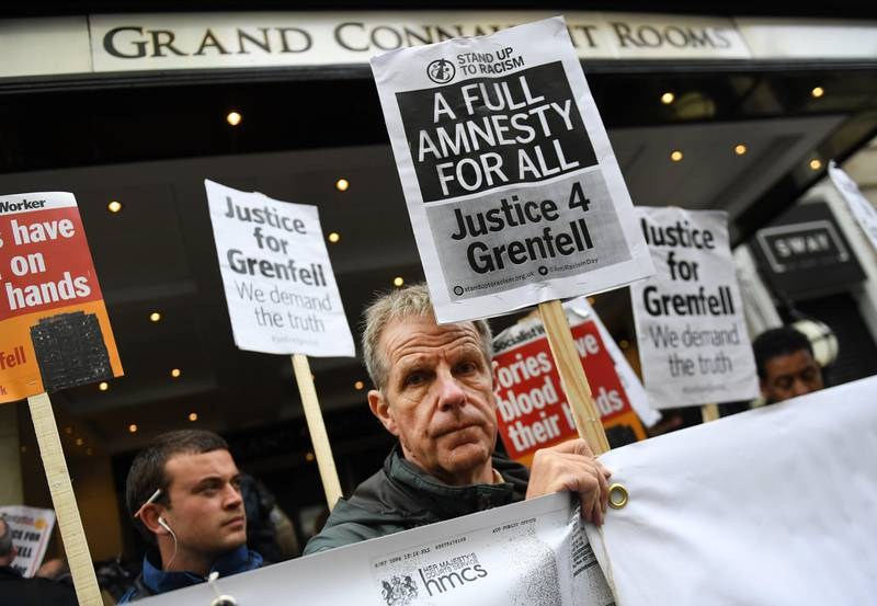 epa06203751 Protesters demonstrate outside the Grenfell Inquiry in London, Britain, 14 September 2017.  Retired High Court judge Sir Martin Moore-Bick is set to open the public inquiry into the causes of the Grenfell Tower fire. It is believed that around 80 people died in the fire in west London in June 2017.  EPA/ANDY RAIN
