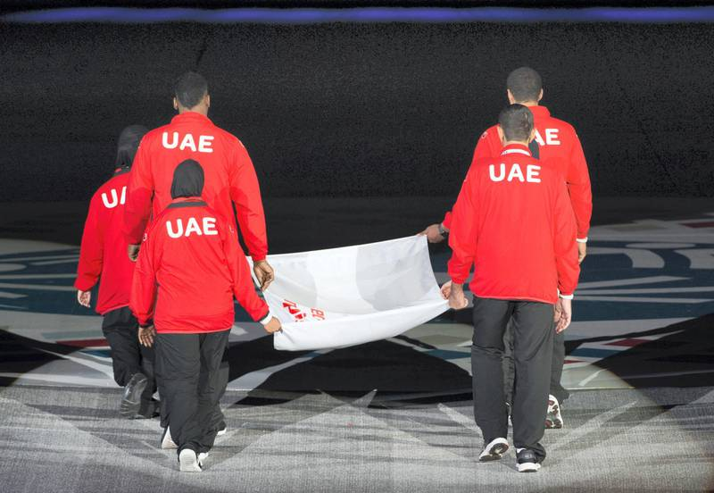 ABU DHABI, UNITED ARAB EMIRATES - March 17, 2018: An athlete raises the Special Olympics flag during the opening ceremony of the Special Olympics IX MENA Games Abu Dhabi 2018, at the Abu Dhabi National Exhibition Centre (ADNEC).( Hamad Al Mansouri for Crown Prince Court - Abu Dhabi )—