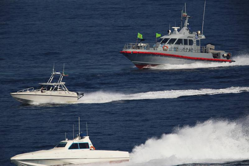 Iranian Revolutionary Guard patrol boats shadow the USS John C. Stennis aircraft carrier on Friday, Dec. 21, 2018. The U.S. aircraft carrier sailed into the Persian Gulf on Friday, becoming the first since America's withdrawal from the Iran nuclear deal and breaking the longest carrier absence in the volatile region since at least the Sept. 11 terror attacks. (AP Photo/Jon Gambrell)