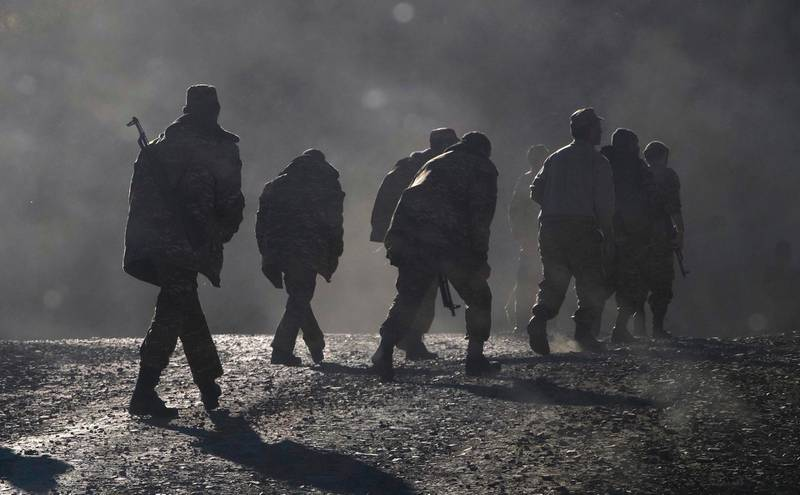 """Ethnic Armenian soldiers walk along the road near the border between Nagorno-Karabakh and Armenia, Sunday, Nov. 8, 2020. Azerbaijan's president says forces have taken control of the strategically key city of Shushi in Nagorno-Karabakh, but a Armenian Defense Ministry spokesman said on Facebook that """"fighting in Shushi is continuing."""" Nagorno-Karabakh lies within Azerbaijan but has been under control of ethnic Armenian forces backed by Armenia since a separatist war there ended in 1994. (AP Photo)"""