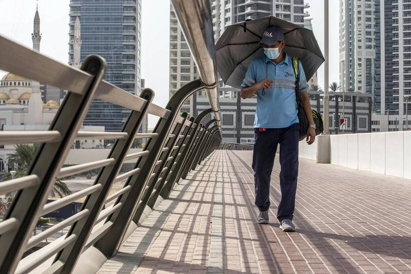 DUBAI, UNITED ARAB EMIRATES. 18 JULY 2020. A man shades himself from the sun while walking along a footpath crossing a bridge in the Dubai marina. Hot and hazy weather in Dubai and the UAE as the full force of summer weather hits during the COVID-19 pandemic with residents unable to easily travel due to the preventative measures put in place. (Photo: Antonie Robertson/The National) Journalist: STANDALONE Section: National.