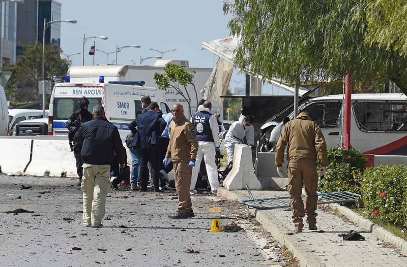 Police and forensic experts inspect the scene of an explosion near the US embassy in the Tunisian capital Tunis on March 6, 2020.  A double suicide attack shook the Tunisian capital as assailants wounded six people including police guarding the US embassy, authorities said. An explosion rocked the Berges du Lac district where the embassy is located around midday, causing panic among pedestrians and motorists in the area. Two assailants died in the attack, the first to hit the capital since June 2019, according to officials.   / AFP / FETHI BELAID