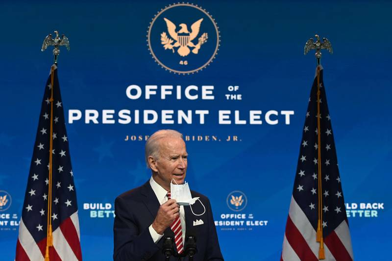 """US President-elect Joe Biden shows a face mask as he answers questions about COVID 19 from the press at The Queen in Wilmington, Delaware on November 16, 2020.  US President-elect Joe Biden expressed frustration on November 16, 2020 about Donald Trump's refusal so far to cooperate on the White House transition process, saying """"more people may die"""" without immediate coordination on fighting the coronavirus pandemic. / AFP / ROBERTO SCHMIDT"""