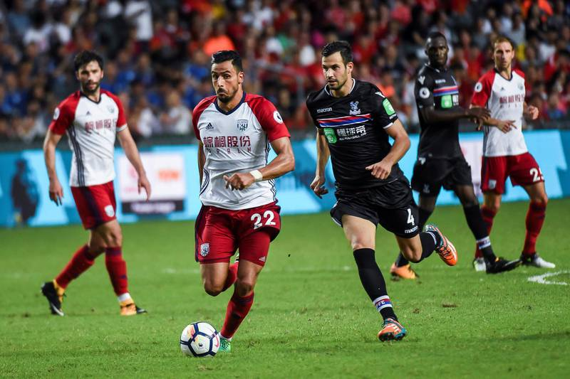 Nacer Chadli (centre L) of West Bromwich Albion controls the ball as Luka Milivojevic (centre R) of Crystal Palace gives chase during the third-place playoff match of the Premier League Asia Trophy football tournament between West Bromwich Albion and Crystal Palace in Hong Kong on July 22, 2017. / AFP PHOTO / ISAAC LAWRENCE / RESTRICTED TO EDITORIAL USE. No use with unauthorized audio, video, data, fixture lists, club/league logos or 'live' services. Online in-match use limited to 75 images, no video emulation. No use in betting, games or single club/league/player publications.