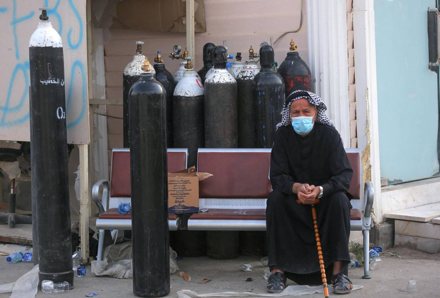 An Iraqi man waits next to oxygen bottles for his wife who is a patient with COVID-19 at the Ibn Al-Khatib Hospital in Baghdad, on April 25, 2021, after a fire erupted in the medical facility reserved for the most severe coronavirus cases. At least 23 people died when a fire broke out in a coronavirus intensive care unit in the capital of Iraq, a country with long-dilapidated health infrastructure facing mounting COVID-19 cases. / AFP / AHMAD AL-RUBAYE