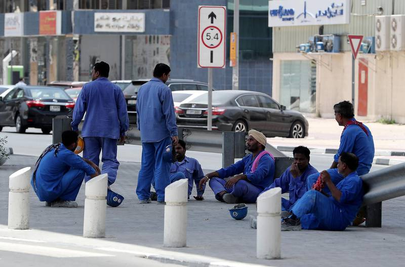 DUBAI , UNITED ARAB EMIRATES , JUNE 14 – 2018 :- Labourers waiting for their staff bus after the midday break at one of the construction site in Al Garhoud area in Dubai. ( Pawan Singh / The National )  For News. Story by Ramola