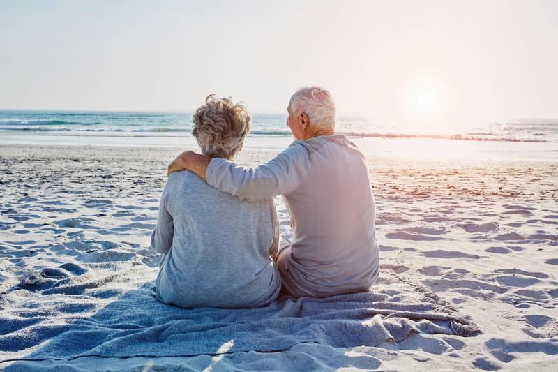 Südafrika, Kapstadt, Strand, Familie, Urlaub, Reisen, Senioren-Paar sitzt am Strand und schaut auf das Meer