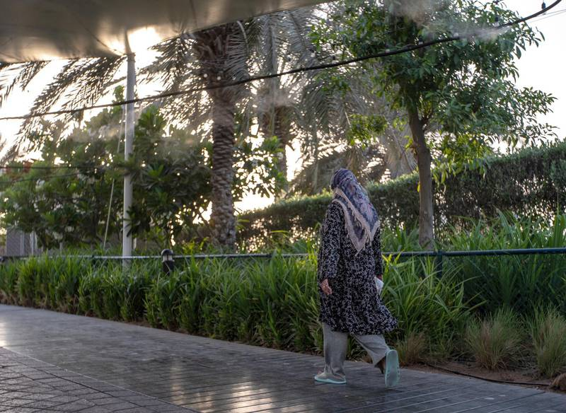 Abu Dhabu residents walk along the Corniche where a misting system is attached along the walkway to help beat the heat and humidity this summer on June 26th, 2021. Victor Besa / The National.