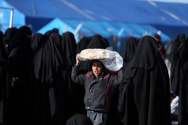 A boy carries bread on his head at al-Hol displacement camp in Hasaka governorate, Syria April 2, 2019. Picture taken April 2, 2019. REUTERS/Ali Hashisho