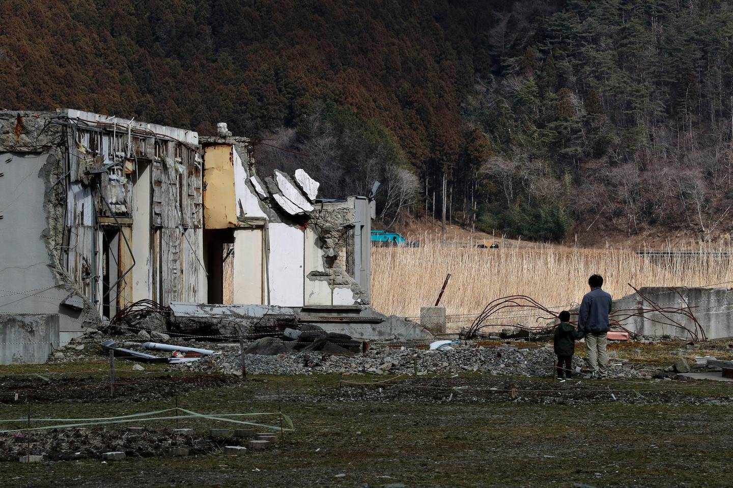 epa06593218 A boy and his father stand taking a moment at the remains of the Okawa Elementary School destroyed by the tsunami in Ishinomaki, Miyagi Prefecture, 10 March 2018, the eve of the seventh anniversary of the 9.0-magnitude earthquake and subsequent tsunami. In the school, 74 students and 10 teachers were killed by the tsunami following the magnitude 9.0 earthquake on the way of their evacuation. The seventh anniversary of the 9.0-magnitude earthquake and subsequent tsunami that devastated northeastern Japan and triggered a nuclear disaster at Tokyo Electric Power Company's Fukushima Daiichi Nuclear Power Plant will be marked on 11 March 2018.  EPA/KIMIMASA MAYAMA
