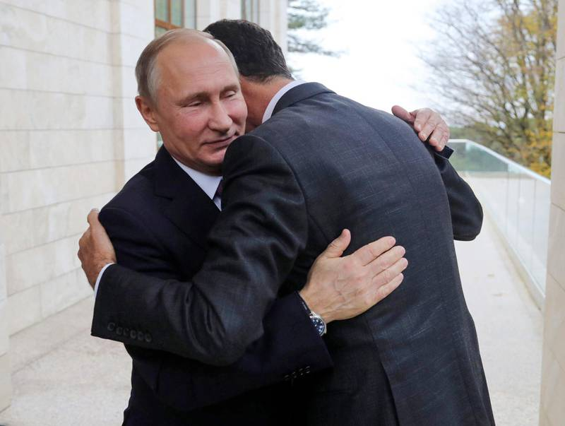 In this Monday, Nov. 20, 2017, photo, Russian President Vladimir Putin, left, hugs with Syrian President Bashar Assad in the Bocharov Ruchei residence in the Black Sea resort of Sochi, Russia. Putin has met with Assad ahead of a summit between Russia, Turkey and Iran and a new round of Syria peace talks in Geneva, Russian and Syrian state media reported Tuesday. (Mikhail Klimentyev, Kremlin Pool Photo via AP)