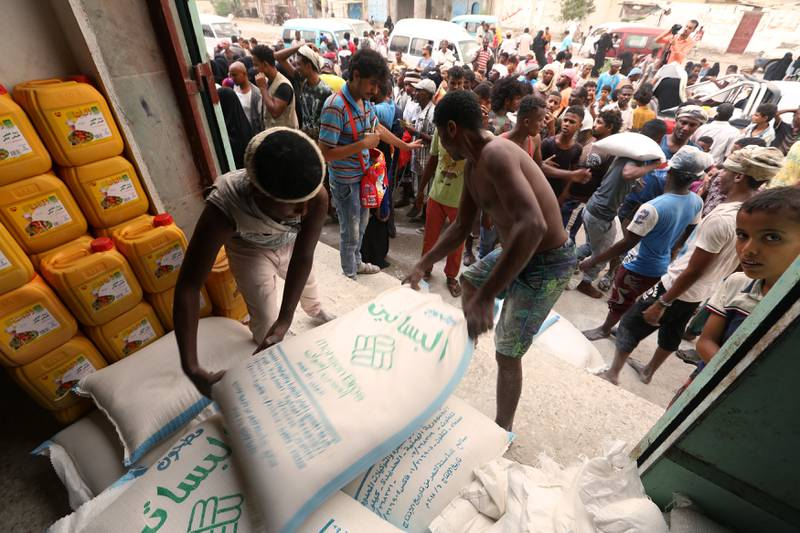 Workers unload sacks of wheat flour as people gather outside an aid distribution centre in the Red Sea port city of Hodeidah, Yemen June 14, 2018. REUTERS/Abduljabbar Zeyad