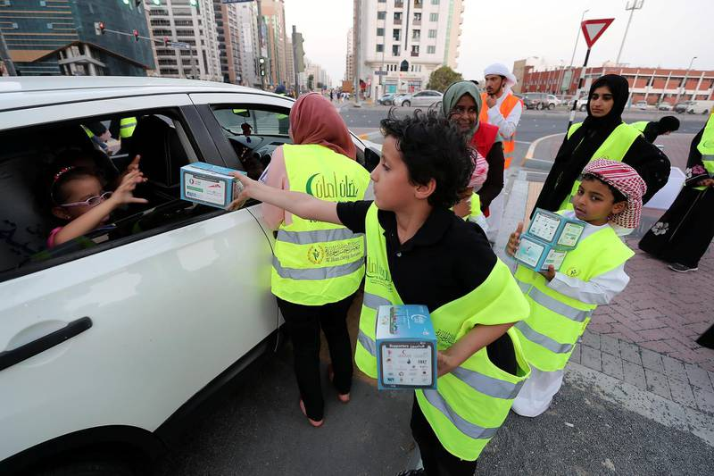 ABU DHABI , UNITED ARAB EMIRATES , MAY 29 – 2018 :- Young volunteer Iyad giving iftar boxes to the motorist at the Al Wahda Mall signal in Abu Dhabi.  ( Pawan Singh / The National )  For News. Story by Omnia Al Saleh