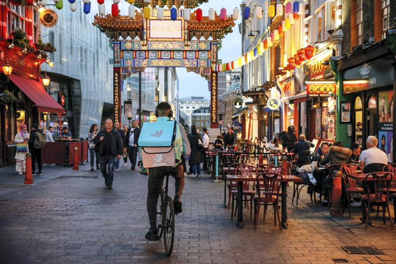 A takeaway food courier, working for Deliveroo, operated by Roofoods Ltd., stops in the Chinatown district of London, U.K., on Tuesday, Sept. 29, 2020. Covid-19 lockdown enabled online and app-based grocery delivery service providers to make inroads with customers they had previously struggled to recruit, according the Consumer Radar report by BloombergNEF. Photographer: Hollie Adams/Bloomberg via Getty Images
