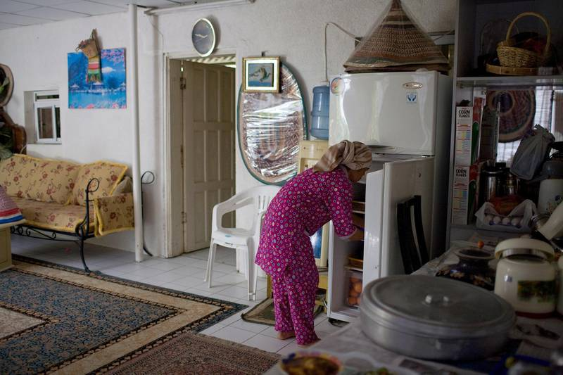 FUJAIRAH, UNITED ARAB EMIRATES - March 14, 2008: A maid gathers food from a fridge while preparing lunch. (Photo by Philip Cheung / Abu Dhabi Media Company ) *** Local Caption *** PC056-Fujfamily.JPG