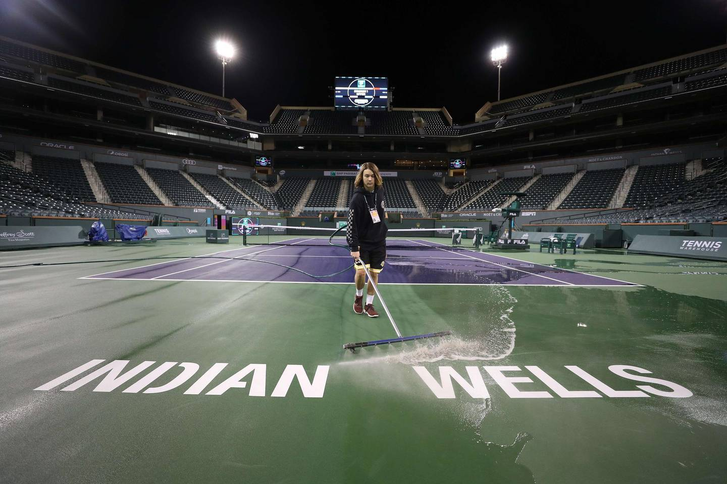 INDIAN WELLS, CALIFORNIA - MARCH 08: Courtmaster Jeffrey Brooker cleans the center court at the Indian Wells Tennis Garden on March 08, 2020 in Indian Wells, California. The BNP Paribas Open was cancelled by the Riverside County Public Health Department, as county officials declared a public health emergency when a case of coronavirus (COVID-19) was confirmed in the area.   Al Bello/Getty Images/AFP == FOR NEWSPAPERS, INTERNET, TELCOS & TELEVISION USE ONLY ==