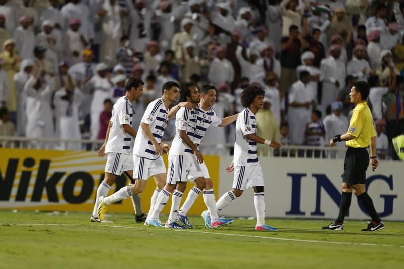 Palyers from UAE's Al-Ain club celebrate after scoring a goal against Qatar's Al-Rayyan club during their AFC Champions League football match in the eastern Emirati city of Al-Ain on April 3, 2013. AFP PHOTO /KARIM SAHIB  *** Local Caption ***  832404-01-08.jpg