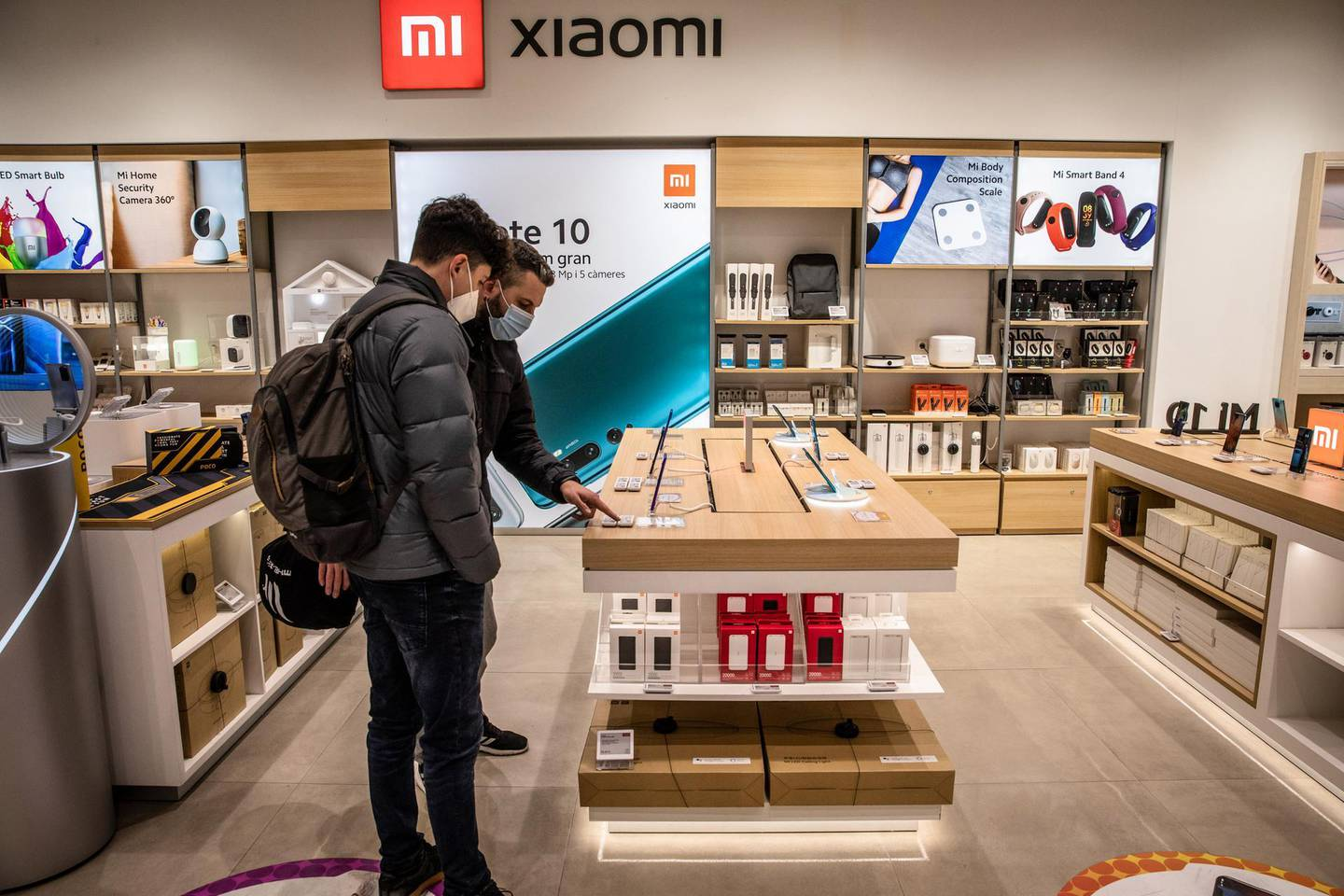 Customers browse Xiaomi Corp. smartphones on display inside the AliExpress plaza retail store, operated by Alibaba Group Holding Ltd., in Barcelona, Spain, on Wednesday, Jan. 13, 2020. U.S. officials deliberated but ultimately decided against banning American investment in Alibaba and Tencent Holdings Ltd., a person familiar with the discussions said, removing a cloud of uncertainty over Asia's two biggest corporations. Photographer: Angel Garcia/Bloomberg
