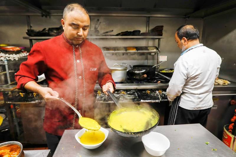 A kitchen worker plates up a curry dish in the kitchen of the Indo Indian fine dining restaurant in Chobham, U.K., on Wednesday, Nov. 14, 2018. Almost two decades afterchicken tikka masala was unofficially declared Britain's national dish, pro-Leave politicians promised restaurants higher inflows from South Asia with easier visa rules, shutting the door on European workers, allowing lower salary-thresholds to hire overseas staff and even regularizing undocumented workers. Photographer: Luke MacGregor/Bloomberg